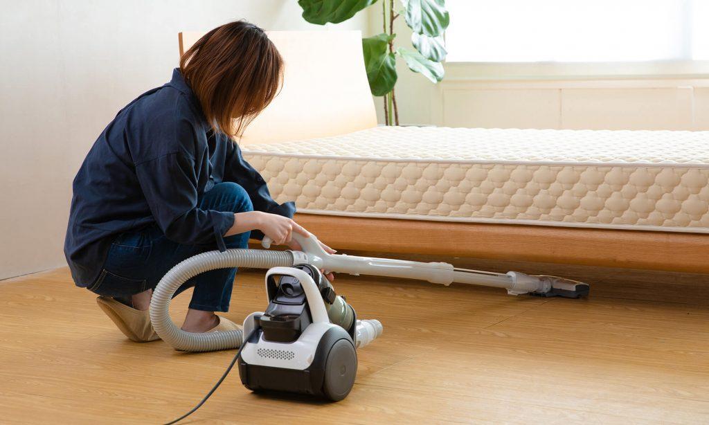ベッド下に掃除機をかけて仕上げを行う